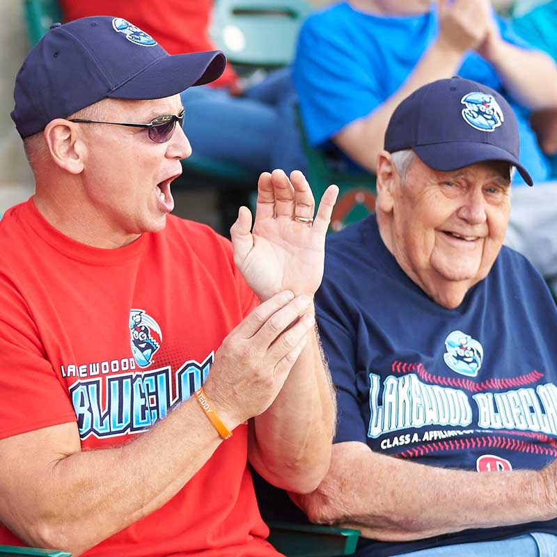 young man and elderly man at blueclaw baseball game cheering and smiling