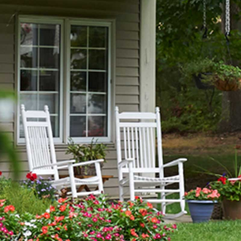 home with two white rocking chairs on porch and flowers