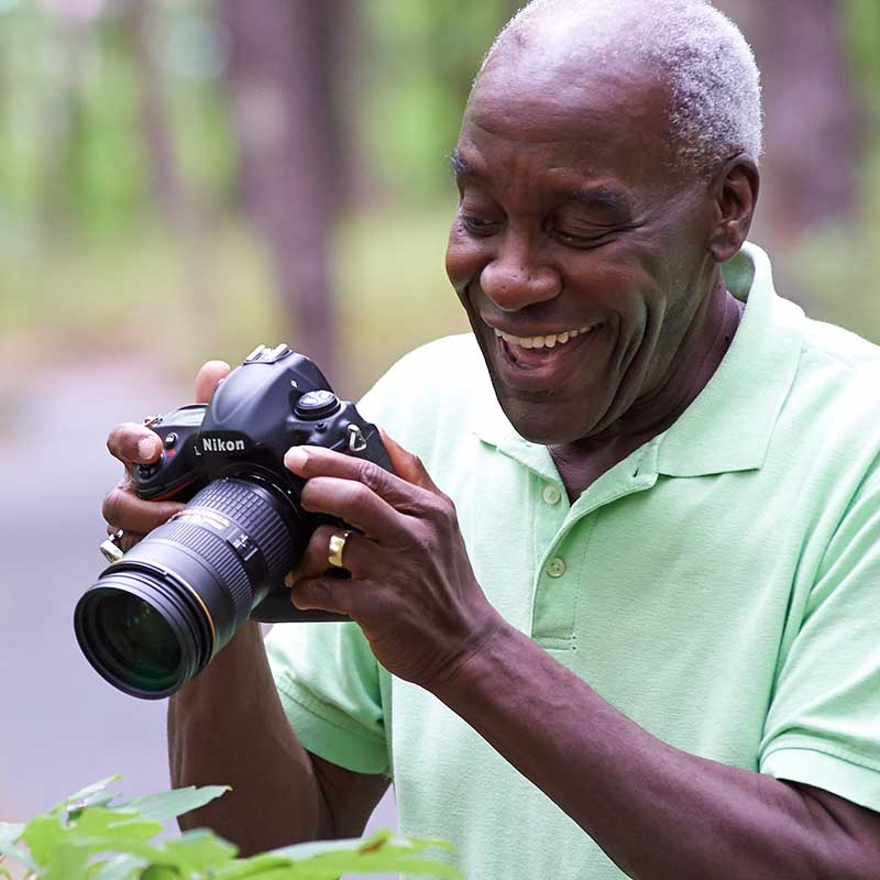 older man laughing and taking photos with nikon camera outside