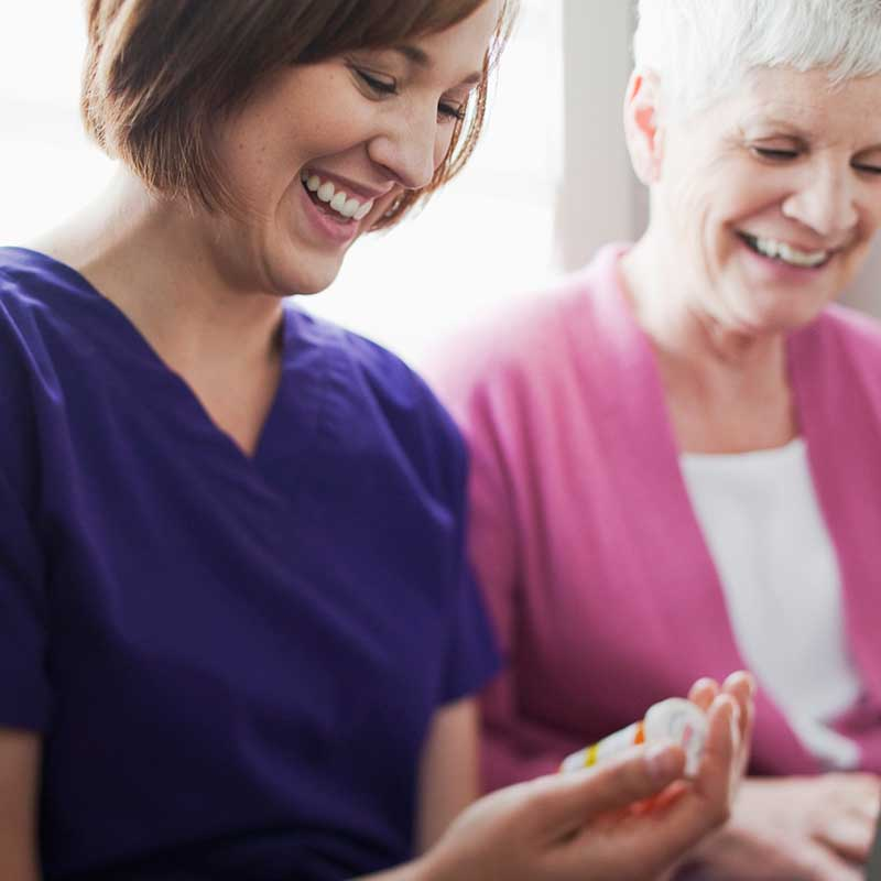 health services admin holding pill bottle and laughing with patient