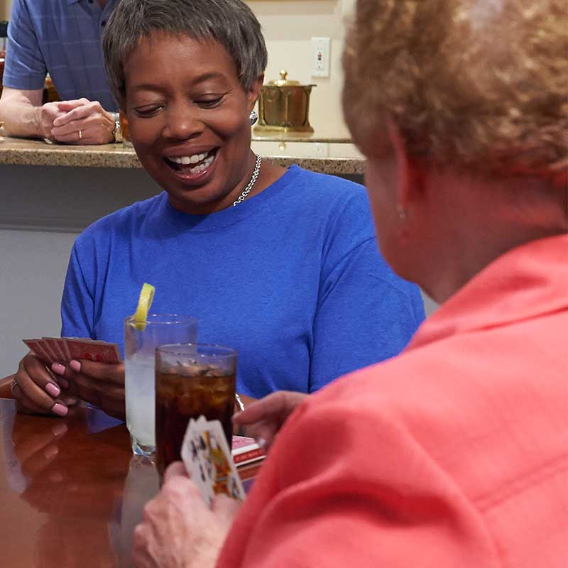 elderly woman in blue shirt smiling and playing cards with friends