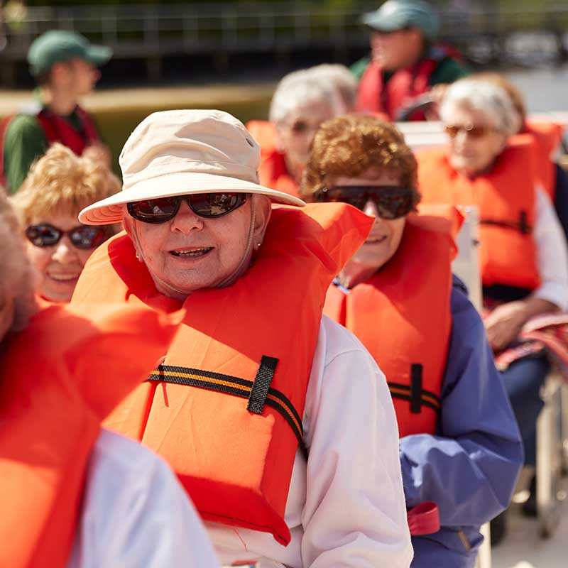 seniors on boat with orange life jackets
