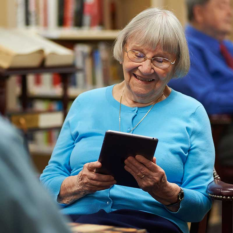 elderly woman smiling and using tablet in library