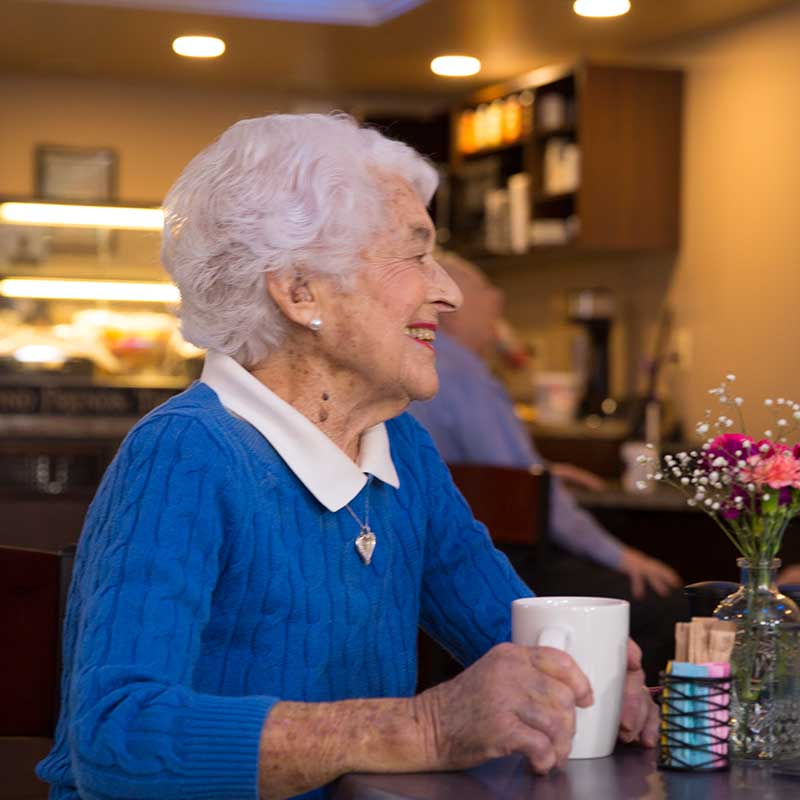 elderly woman drinking coffee in cafe and smiling
