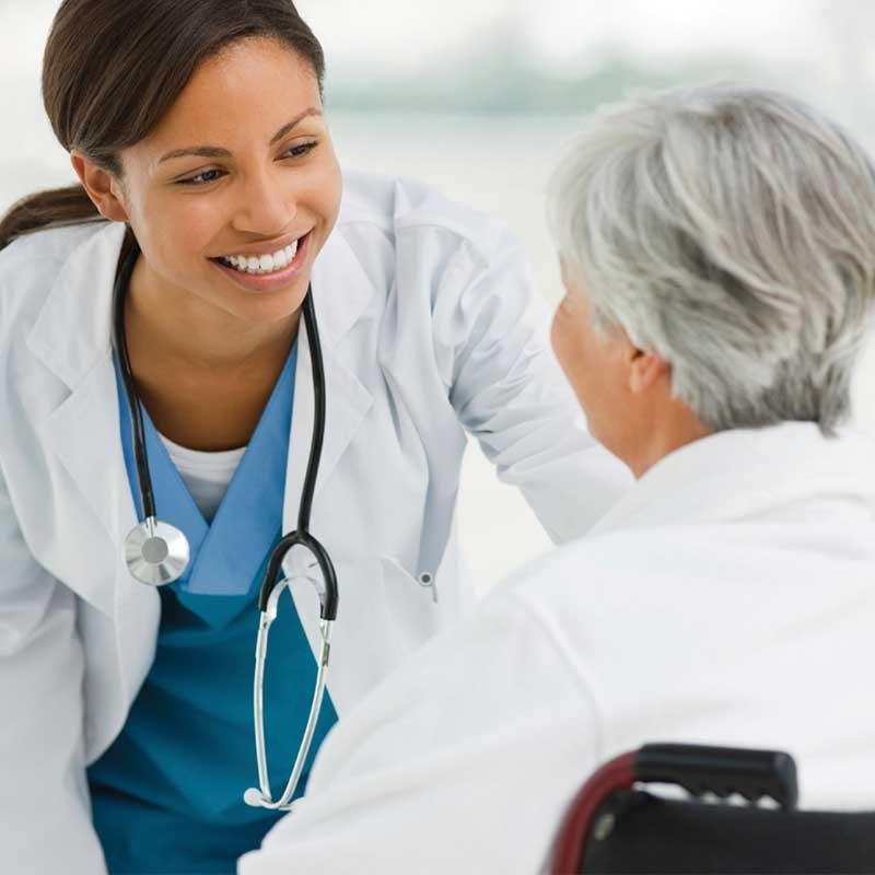 skilled nursing doctor smiling at elderly woman in wheelchair