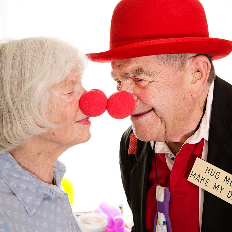 elderly couple touching red clown noses