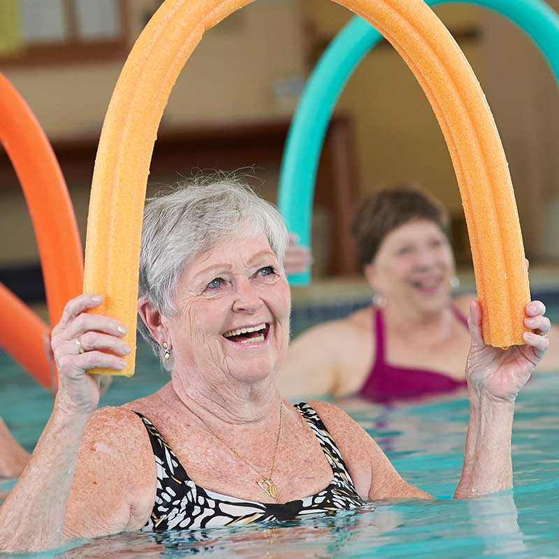 elderly women smiling in pool while doing water aerobics with noodle