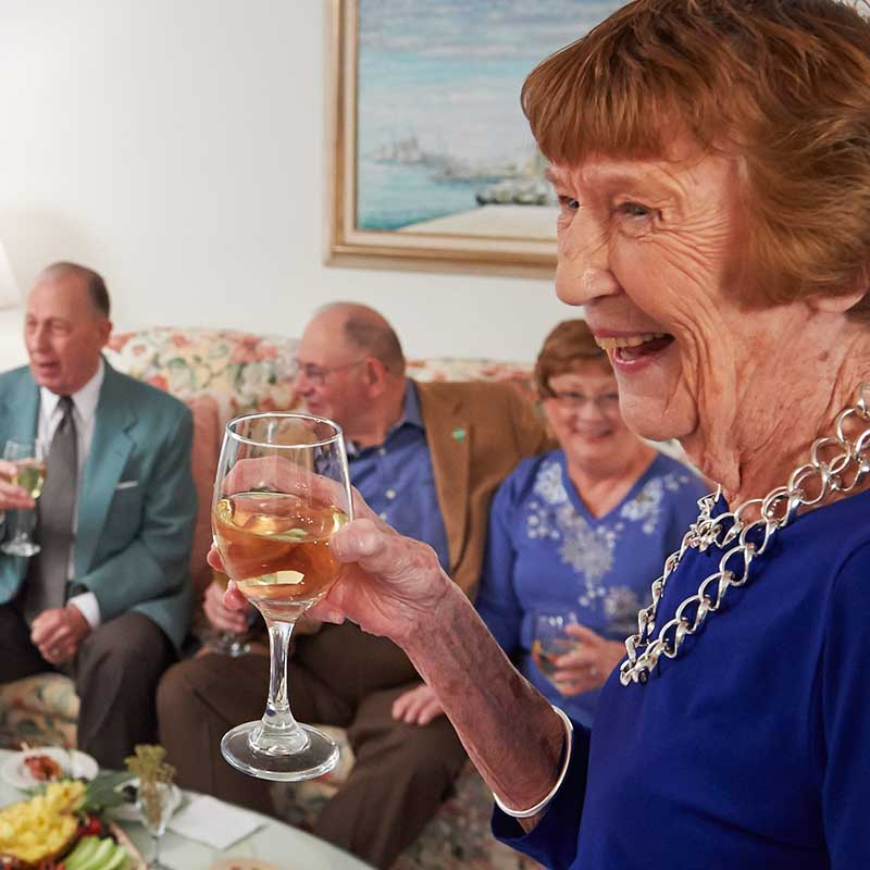 elderly woman with friend laughing and drinking in living room