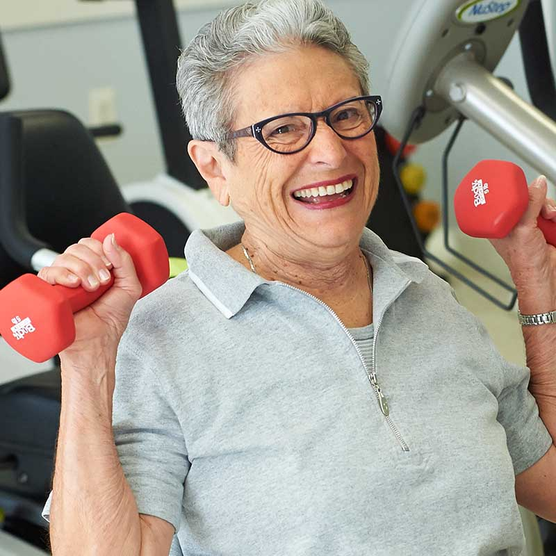 elderly woman with glasses smiling and lifting weights in gym